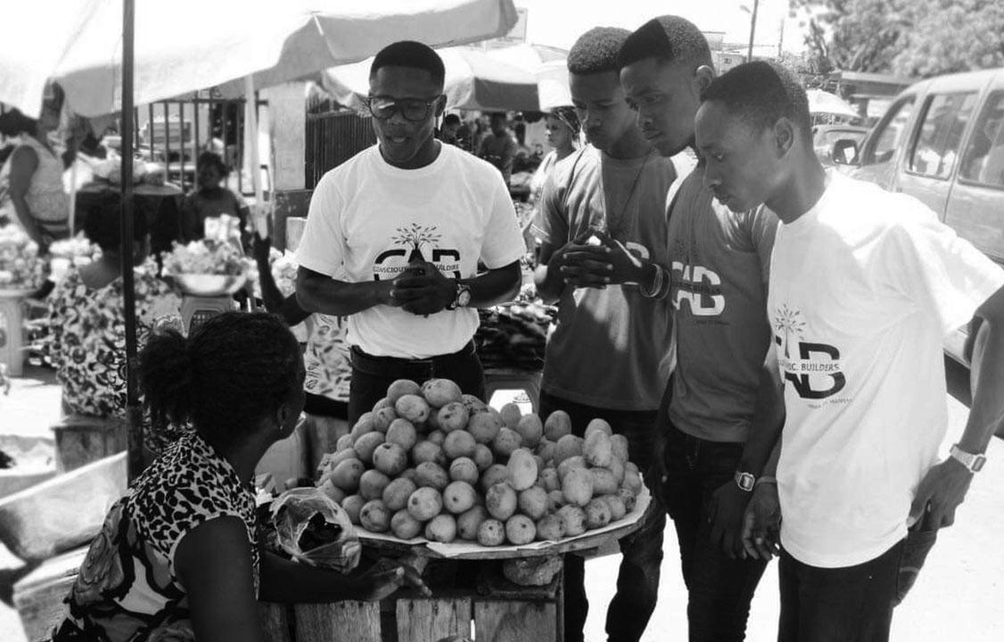 CAB Consult members interacting with a trader at the Kotokuraba Market