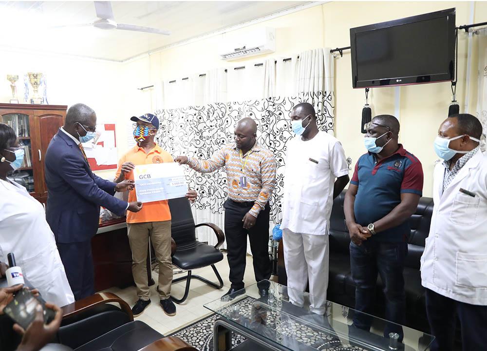 President of GAUA-UCC presenting a dummy cheque to Dr. Evans Ekanem