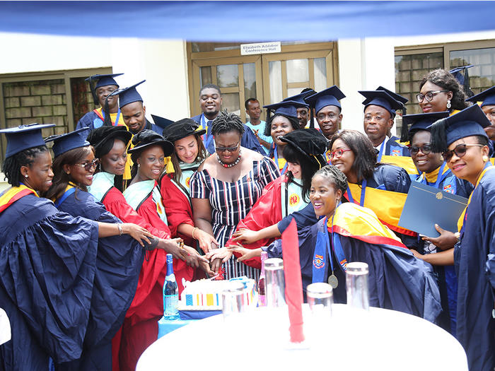 Pro Vice-Chancellor with the graduates cutting the graduation cake