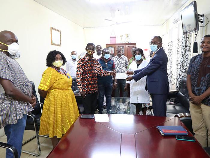 Dr. Boadi-Kusi presenting the cheque to Dr. Evans Ekanem