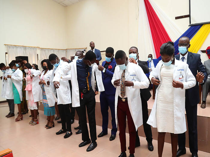 Students being robed with the white coat at the ceremony